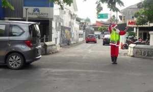 Supeltas yang bertugas di perempatan Wora-wari Kawasan Kalitan, Solo, Martin Hidungoran, 36, mengatur lalu lintas mengenakan baju Sinterklas, Minggu (24/12/2017). (Hijriyah Al Wakhidah/JIBI/Solopos)
