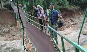Sukarelawan melewati jembatan gantung di Desa Kedungbendo, Kecamatan Arjosari yang hampir roboh untuk menyalurkan bantuan ke warga terdampak bencana, Minggu (3/12/2017). (Istimewa/polrespacitan.com)