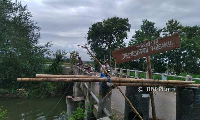 Pengendara melintas di jembatan Dengkeng Ngoreyan di Desa Ngandong, Kecamatan Gantiwarno, Klaten, Sabtu (2/12/2017). Penyangga jembatan putus karena tergerus air. (Cahyadi Kurniawan/JIBI/Solopos)