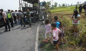 Masyarakat menyaksikan sisa bis yang terbakar di jalan Wates km 12, Argorejo, Sedayu, Rabu (27/12/2017). (Harian Jogja/Herlambang Jati Kusumo)