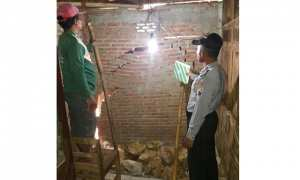Aparat Polsek Paranggupito meninjau rumah yang terdampak tanah ambles di Tompak, Ketos, Paranggupito, Wonogiri, Minggu (21/1/2018). (Istimewa/Polres Wonogiri)