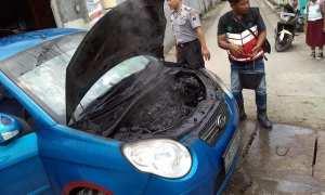 Polisi dan warga memadamkan api pada mesin bagian depan mobil KIA Picanto milik warga Bentak, Sidoharjo, yang terbakar di pinggir Jalan Solo-Sragen, Jati, Masaran, Sragen, Selasa (23/1/2018). (Istimewa/Mujiono/Polsek Masaran)