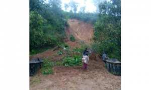Warga melintas di timbunan tanah longsor di ujung jembatan Plumbon Hargosari, Tirtomoyo, Wonogiri, Kamis (25/1/2018) pagi. (Istimewa/BPBD Wonogiri)