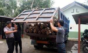 Sejumlah polisi membuka pintu bak dump truck berisi 32 batang kayu jati curian di halaman Mapolsek Jenar, Sragen, Kamis (25/1/2018). (Tri Rahayu/JIBI/Solopos)