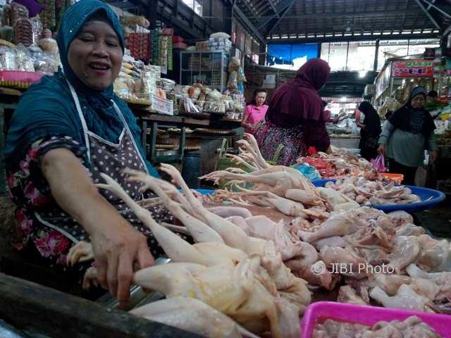 Salah satu pedagang di Pasar Gede, Warti, menata daging ayam ras di losnya, Sabtu (13/1/2018). Harga daging ayam ras di pasar tersebut senilai Rp35.000/kilogram (kg). (Danur Lambang Pristiandaru/JIBI/SOLOPOS)