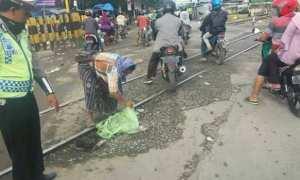 Seorang wanita menaruh material demi menutup lubang jalan di perlintasan kereta api dekat Pasar Ganefo, Kecamatan Mranggen, Kabupaten Demak, Jateng. (Facebook.com-Iwan Ubaidillah)