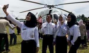 Pelajar ber-selfie di depan helikopter yangcditumpangi Menteri Pertanian Amran Sulaiman ke Demak, Jateng, Selasa (23/1/2018). (Okezone.com-Taufik Budi)