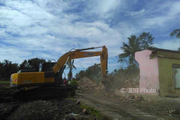Warga melihat alat berat sedang merobohkan sebuah rumah milik warga di atas lahan Izin Penetapan Lokasi New Yogyakarta International Airport (NYIA), Desa Kragon II, Desa Palihan, Senin (8/1/2018). (Uli Febriarni/JIBI/Harian Jogja)