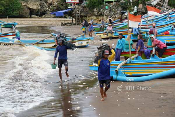 Nelayan mengangkat mesin kapal seusai melaut di kawasan pantai Baron, Kemadang, Tanjungsari. (Harian Jogja/Herlambang Jati Kusumo)