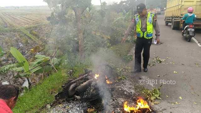 Anggota Polsek Sidoharjo, Sragen, melihat kondisi motor Honda Vario milik Soyo, 41, warga Brojol, Miri, Sragen, yang terbakar, Selasa (6/2/2018). (Istimewa/Polsek Sidoharjo/Agus Taruna)