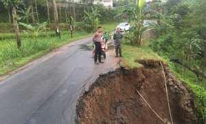 Petugas polisi dan TNI mengecek ruas jalan di Bulurejo, Bulukerto, Wonogiri, yang longsor, Senin (12/2/2018) pagi. (Istimewa/Polres Wonogiri)