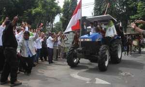 Pasangan cabup-cawabup, Rohadi Widodo-Ida Retno Wahyuningsih, mengendarai traktor menuju Kantor DPRD Karanganyar, Selasa (13/2/2018). (M. Ferri Setiawan/JIBI/Solopos)