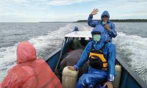 Tim Deru mengenakan jas hujan akibat cuaca yang tidak menentu saat melakukan perjalanan dengan perahu menuju Asmat. (IST/Dok Tim Deru UGM)