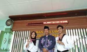 Nafisha Nugraha Putri (kiri) dan Muhammad Daffa (kanan), siswa MAN 4 Bantul yang berprestasi di bidang taekwondo berfoto bersama Kepala Sekolah Mohamad Yusuf (tengah), Kamis (22/2/2018). (Rheisnayu Cyntara/JIBI/Harian Jogja)