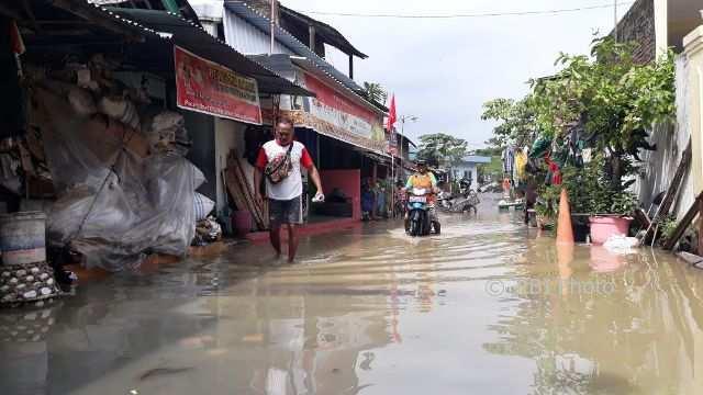 Warga melintasi genangan air di Pucangsawit RT 003 RW 006, Pucangsawit, Jebres, Solo, Kamis (8/2/2018). (Nicolous Irawan/JIBI/SOLOPOS)