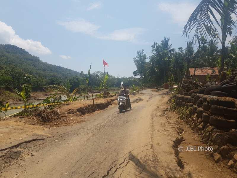 Warga melintasi jalan penuh rekahan di Dusun Sompok, Bantul, Minggu (11/2/2018). (Harian Jogja/Salsabila Annisa Azmi)
