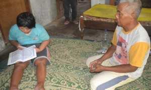 Fitri Rejeki (kiri), warga Kampung Ngluwang, Kriwen, Sukoharjo, membaca Alquran ditemani bapaknya, Sukarno, di rumahnya, Jumat (16/2/2018).(Bony Eko Wicaksono/JIBI/Solopos)