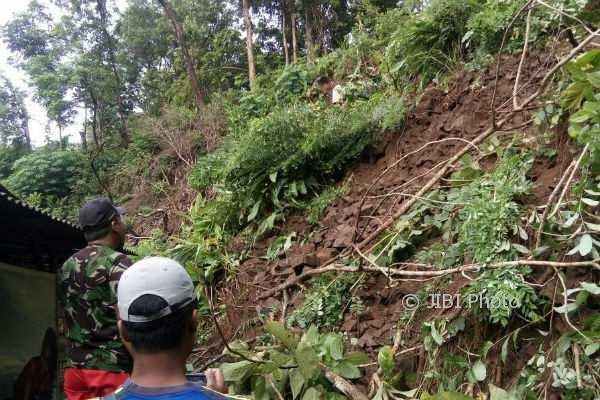 Warga bergotong royong membersihkan material longsor dan memotong pohon tumbang yang mengenai tembok rumah Tugiman, warga Padukuhan Alasgede RT 08, Dusun Kaligatuk, Desa Srimulyo, Kecamatan Piyungan, Jumat (2/2/2018). (Rheisnayu Cyntara/JIBI/Harian Jogja)