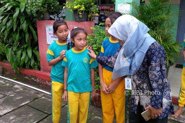 Kepala SD Negeri II Jetisharjo, Temu Lestari (kiri) sedang berbincang dengan para siswi yang sempat mengalami gejala keracunan setelah makan permen. (Ujang Hasanudin/JIBI/Harian Jogja)