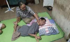 Yudo Utomo, 34, berbaring ditemani ibunya, Kasih, di rumahmereka diGang Punden Jl. Gajahmada, Kelurahan Winongo, Kecamatan Manguharjo, Kota Madiun, Jumat (9/2/2018) siang. (Abdul Jalil/JIBI/Madiunpos.com)