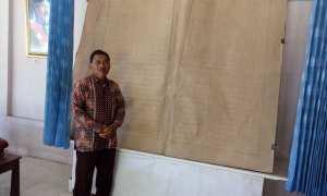 Suradi Joyonagoro berpose di dekat mushaf Alquran 30 juz bertuliskan tangan di kediamannya, Makamhaji, Kartasura, Sukoharjo, Jumat (2/3/2018). (Iskandar/JIBI/Solopos)