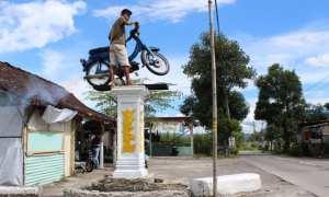 Warga menghidupkan mesin sepeda motor yang terpasang di tugu buatan warga Desa Prawatan, Kecamatan Jogonalan, Selasa (20/2/2018). (Taufiq Sidik/JIBI/Solopos)