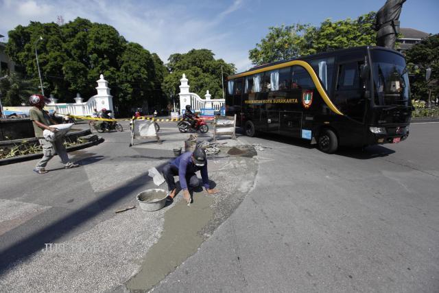 Pekerja memperbaiki ornamen di bundaran gladak yang mengalami kerusakan akibat tak kuat menahan beban volume kendaraan yang melintas (Agoes Rudianto/JIBI/Solopos)