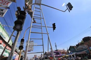Pekerja melakukan pemasangan lampu traffic light baru di perempatan Kartasura, Sukoharjo, Selasa (30/7). Penggantian lampu APILL tersebut segera akan difungsikan untuk kelancaran lalulintas mudik Lebaran