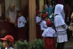 Sejumlah orang tua siswa baru menemani anak mereka saat hari pertama masuk sekolah di SD Negeri 02 Malangjiwan, Colomadu, Karanganyar, Senin (15/7). Sebagian siswa baru kelas 1 harus dibujuk dan ditemani orang tua mereka untuk beradaptasi di sekolah baru.