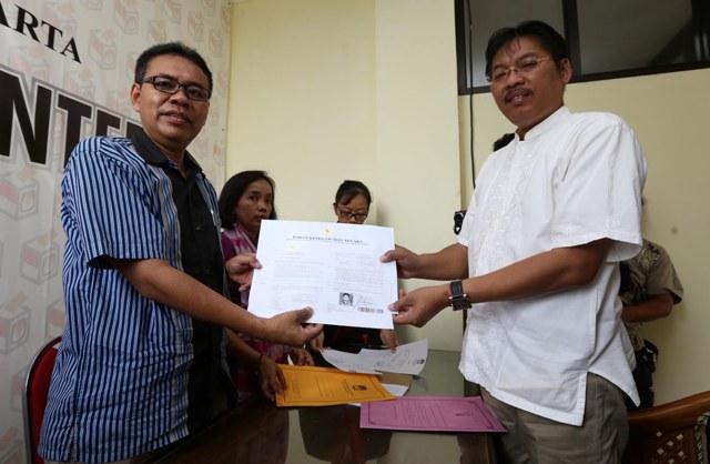 Anung Indro Susanto (kanan), menyerahkan salinan berkas surat keputusan (SK) pensiun dini sebagai pegawai negeri sipil (PNS) kepada Ketua KPU Solo, Agus Sulistyo (kiri), di Kantor KPU Solo, Selasa (20/10/2015). (Solopos/Dok)
