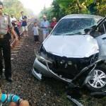Polres Karanganyar Polisi dan masyarakat berkerumun di sekitar lokasi kecelakaan tertabraknya mobil Xenia oleh kereta, di perlintasan tanpa palang di Desa Wonorejo, Gondangrejo, Karanganyar, Minggu (27/3/2016) pagi. (Istimewa/Polres Karanganyar)