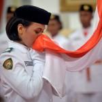 Anggota Pasukan Pengibar Bendera Pusaka (Paskibraka) Nasional 2016 asal Sulawesi Barat Ade Yuliana mencium bendera Merah Putih saat upacara pengukuhan yang dipimpin Presiden Joko Widodo di Istana Negara, Jakarta, Senin (15/8). Presiden mengukuhkan 67 anggota Paskibraka, dari 68 siswa calon Pasukan Pengibar Bendera Pusaka (Paskibraka) Nasional 2016 yang terpilih untuk melakukan upacara pengibaran dan penurunan Bendera Merah Putih saat peringatan 71 tahun Kemerdekaan Indonesia di Istana Merdeka pada 17 Agustus mendatang. (JIBI/Solopos/Antara/Yudhi Mahatma)
