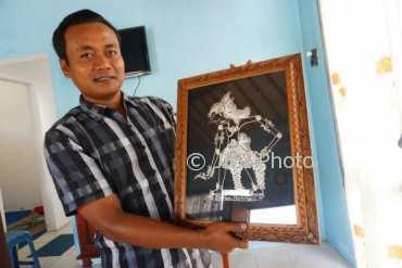 Sekretaris Desa Sodo, Dadang Nugroho menunjukan salah satu hasil kerajinan perak, di Galeri perak, Desa Sodo, Paliyan. (Harian Jogja/Herlambang Jati Kusumo)