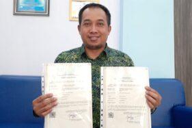 Direktur Politeknik Negeri Madiun (PNM), Muhamad Fajar Subkhan, menunjukkan dua sertifikat paten hasil penelitian dosen PNM, Rabu (2/10/2019). (Abdul Jalil/Madiunpos.com)