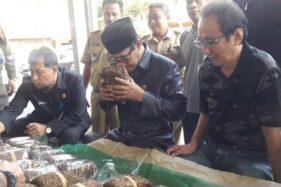 Bupati Temanggung M. Al Khadziq mencium tembakau dalam kunjungan ke salah satu gudang tembakau di Temanggung, Jawa Tengah, Selasa (15/10/2019). (Antara-Heru Suyitno)