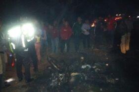 Polisi dan warga melihat sepeda motor yang terbakar di jalan raya Madiun-Surabaya, Desa Sugihwaras, Kecamatan Saradan, Kabupaten Madiun, Sabtu (12/10/2019). (Istimewa-Polres Madiun)