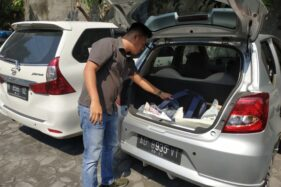Kanit Reskrim Polsek Laweyan Iptu Salman Farizi mengecek barang-barang dalam mobil yang terparkir di Sondakan, Laweyan, Solo, Selasa (21/10/2019) siang. (Solopos-Ichsan Kholif Rahman)