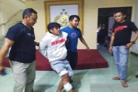 Jumari, 30, tersangka pembunuh Kumalasroh, 25, dipapah oleh aparat Polres Pekalongan setelah ditembak kakinya, Jumat (18/10/2019). (Antara-Kutnadi)