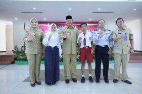 Wali Kota Madiun, Maidi, bersama pelajar menunjukkan kartu elektronik peserta program angkutan sekolah gratis di Wisma Haji setempat, Senin (11/11/2019). (Istimewa-Pemkot Madiun)
