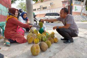 Warinem (kiri), melayani pembeli duriannya di sudut perempatan belakang Kantor DPRD Wonogiri, Kamis (21/11/2019). (Solopos/Rudi Hartono)
