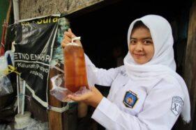 Oxana Firsta menunjukkan es teh yang dibelinya di warung wedagang Pak Sin di Jl. Surya, Purwodningratan, Jebres, Solo, Kamis (21/11/2019). (Solopos/Nicolous Irawan)