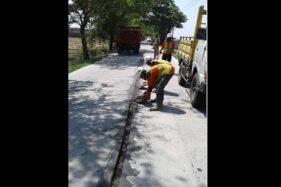 Petugas dari Dinas (PUPR) Sragen menutup rekahan dengan pasir dan aspal di permukaan jalan Tangkil-Kedungupit, Senin (18/11/2019). (Istimewa/Dinas PUPR Sragen)
