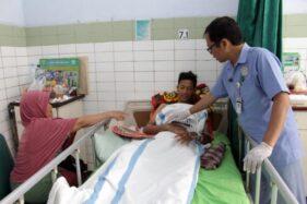 Seorang perawat di Bangsal Mawar RSUD dr. Soehadi Prijonegoro Sragen memeriksa kondisi tangan kanan salah satu pasien korban aula ambruk di SMKN 1 Miri Sragen, Jumat (22/11/2019). (Solopos/Tri Rahayu)