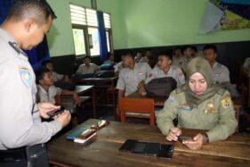 Dua orang petugas Satpol PP Sragen memeriksa tas siswa saat operasi ponsel di SMPN 1 Karangmalang, Sragen, Kamis (14/11/2019). (Solopos/Tri Rahayu)