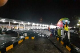 Petugas menyingkirkan bangkai kanopi yang roboh karena diterjang angin di pintu barat Stasiun Madiun, Jumat (13/12/2019) petang. (Abdul Jalil-Madiunpos.com)