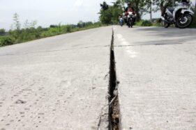 Seorang pengendara jalan melewati menghindari jalan yang retak selebar 5 cm di jalur Tangkil-Kedungupit, Sragen Kota, Sragen, Kamis (12/12/2019). (Solopos/Tri Rahayu)
