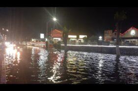 Pengendara melewati jalan depan Mapolres Madiun Kota yang kebanjiran, Jumat (13/12/2019). (Abdul Jalil/Madiunpos.com)