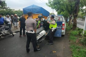 Polisi mengevakuasi sepeda motor korban kecelakaan di depan kantor DPRD Solo, Jumat (13/12/2019). (Solopos/Ichsan Kholif Rahman)