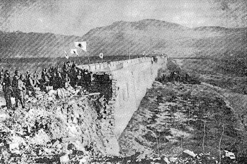 Prajurit Jepang berdiri di atas reruntuhan Gerbang Zhongshan Nanking pada 13 Desember 1937. (Wikimedia.org)