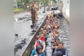 Video pegawai honorer di Jakarta Barat masuk ke got berisi air keruh dan kotor ketika melakukan tes perpanjangan kontrak, viral di media-media sosial. (Suara.com/Facebook)